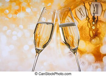 New Year or Christmas at midnight with champagne flutes make cheers, golden bokeh and clock on golden background