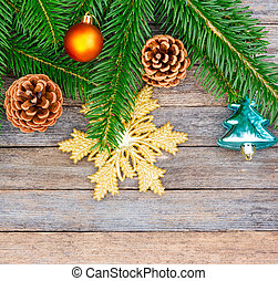 New Year or Christmas background: fir branches, colorful glass balls and golden snow-flake, cones over old wooden backdrop, top view, copy space