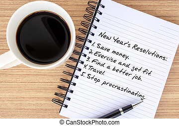 New Year Resolutions list written on notepad with cup of coffee and pen on top of wooden background.