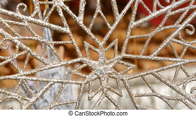 New Year's and Christmas decor. A huge beautiful silver snowflake sways in the wind at Christmas market