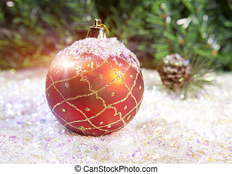 New Year's ball on a background of decorative snow and branch of a fir tree
