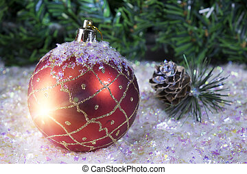 New Year's ball on a background of snow and a fir tree branch
