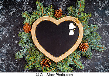 New Year's composition of Christmas tree branches and Christmas tree decorations and a frame in the shape of a heart, top view, place for text, flat lay