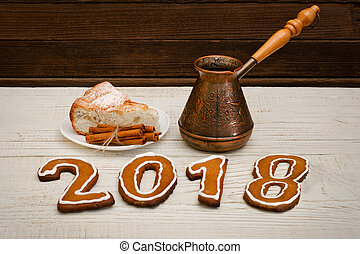 New Year's Concept. The figure in 2017 of gingerbread, pots and apple pie with cinnamon on table