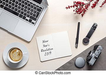New year's resolution 2019 written on open notepad as flatlay