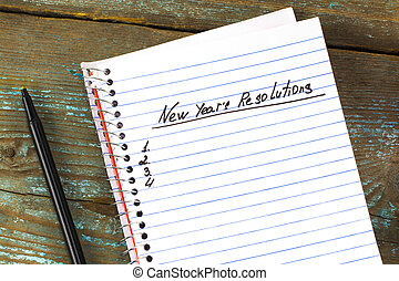 New Year's Resolution written on a notepad and pen. New Year resolutions concept