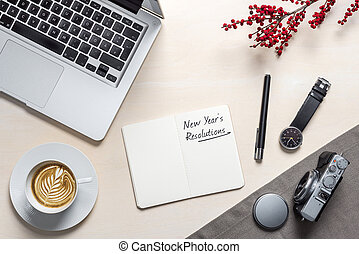 New year's resolution written on notepad in office as flatlay