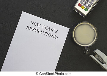 New Year's resolutions paper, a cup of coffee with foam on a black background