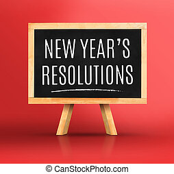 New year's resolutions word on Blackboard with easel on vivid red studio backdrop, New year planning