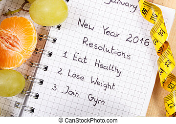 New years resolutions written in notebook and tape measure -...