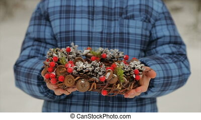 New Year's wreath of cones in the hands of a boy - Christmas...
