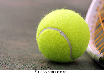 New yellow colored tennis ball placed next to racket(racquet...