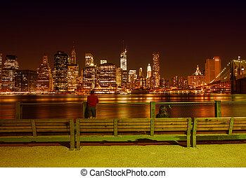 New York City at night in summer. View of Manhattan skyline from Brooklyn Bridge Park.