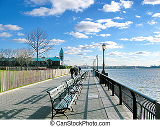 New York City: Battery Park sidewalk on a sunny day, with ...