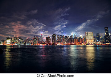 New York City Manhattan midtown panorama at dusk with skyscrapers illuminated over east river