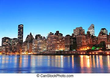 New York City Manhattan midtown skyline at night over East...