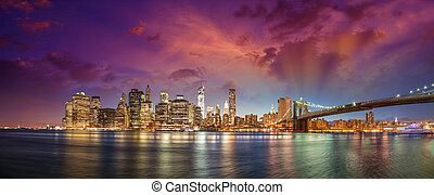 New York City Manhattan skyline panorama with Brooklyn Bridge and office skyscrapers buildings at dusk illuminated with lights at night.