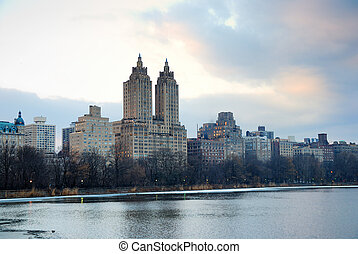 New York City Skyline over lake in Central Park at dusk
