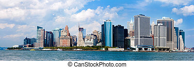 Panorama of the famous landmark view of the Manhattan New York City Skyline with the Financial district, World Trade Center and Wall Street. NYC known as the Big Apple. Metropolitan skyscraper buildings on a sunny day with deep blue sky and white clouds.