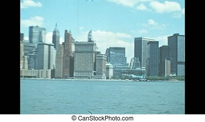 Old Twin Towers skyscrapers and Battery Park of New York city. United States America in 1976. Archival of Manhattan skyline from Hudson river by sightseeing cruise.