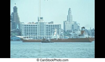 Cargo ship in the Manhattan pier by the old skyline of New York city. United States America in 1976. Archival of Manhattan downtown skyline from Hudson river by sightseeing cruise.