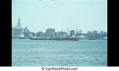 Cargo ship in the skyline the of old New York city. United States America in 1976. Archival of Manhattan downtown skyline from Hudson river by sightseeing cruise.