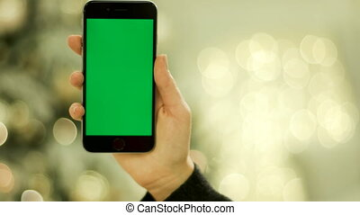Close-up of female hands touching green screen on mobile...
