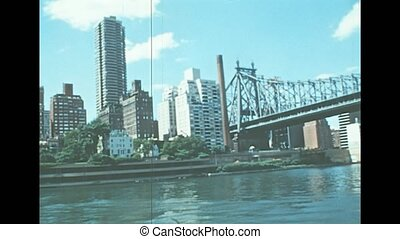 Archival of Long Island skyline by sea view from East river sightseeing cruise in New York. Old house buildings of the old New York city. United States of America in 1976. Vintage USA from 70s.