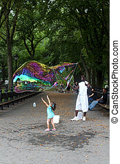 NEW YORK - SEPTEMBER 01: Unidentified performer and kids play with soap bubbles at Central Park, on September 01, 2013, in New York City.