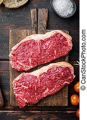 New York steak, raw beef meat , on dark wooden background, top view