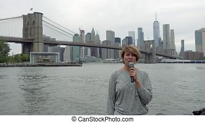 Young woman TV reporter is broadcasting on the background of Manhattan skyscrapers