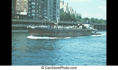 Archival of New York city with cargo ships and tugboat. Sea view from boat tour on East river of Manhattan Upper Bay of New York City in 1976. Archival of Manhattan island.