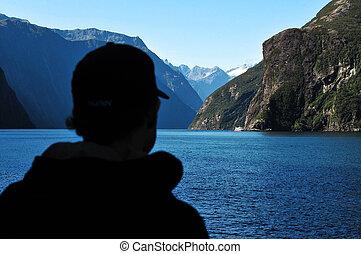 Silhouet of a tourist explores Fiordland, southern New Zealand.