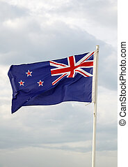 New Zealand flag on a blue sky with clouds background