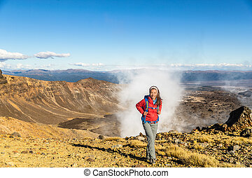 New Zealand Tongariro Alpine Crossing Hiking trek hiker woman with bag and outdoor jacket tramping in volcanic steam vents fumaroles background. Summer travel vacation adventure trekking girl hike.