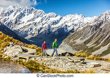 New zealand travel hikers hiking in Mount Cook trail to Mueller Hut. Tramping lifestyle couple tourists walking on alpine route in alps with snow capped mountains in background.