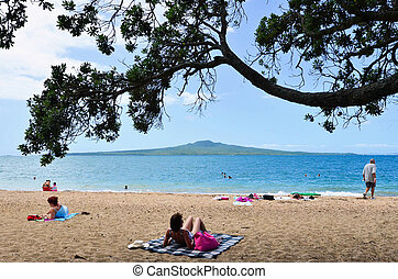 People sunbathing and swim in Devon port beach Auckland with the view of Rangitoto Island in the background.