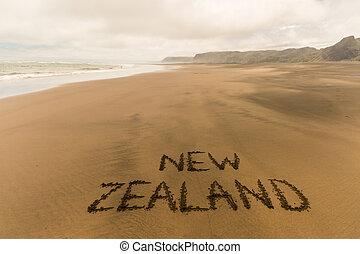 New Zealand written on sandy beach