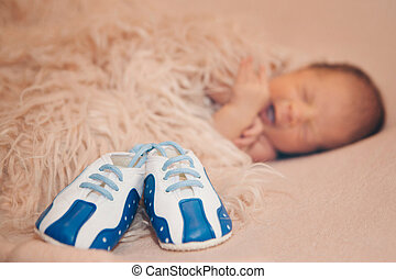 Newborn baby and a pair of baby shoes
