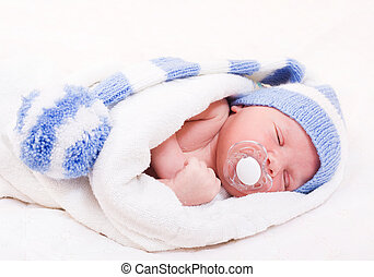 newborn baby (at the age of 7 days) sleeps in a knitted ...