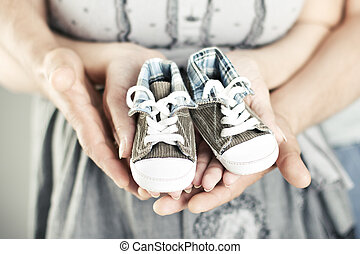 Newborn baby booties in parents hands. Close up.