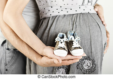 Newborn baby booties in parents hands. Pregnant woman belly.