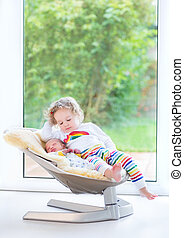 Newborn baby boy and his toddler sister relaxing in a swing next