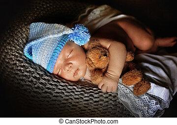 Newborn baby boy asleep wrapped in
