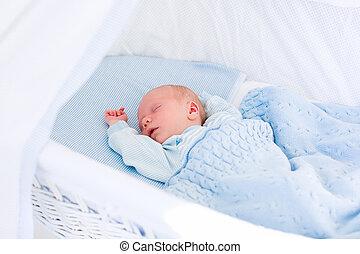 Newborn baby boy in white bassinet