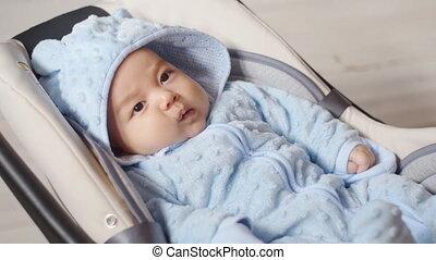 Newborn baby boy sitting in a car seat