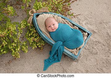 Newborn Baby Boy Sleeping in a Tiny Boat