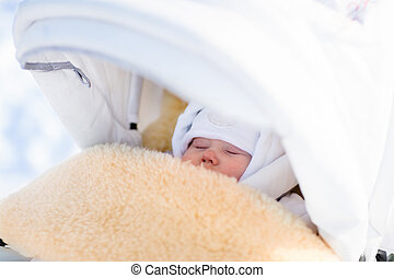 Newborn baby boy sleeping in stroller in winter - Cute...