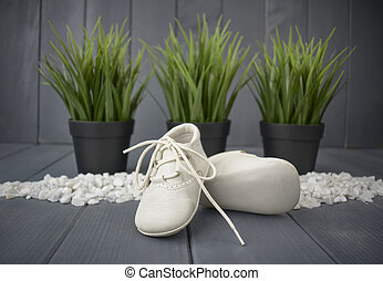 Newborn baby boy's booties in white, with decorative stones, green plants and a gray wooden background. Children's shoes