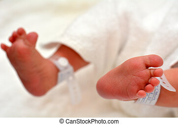 Newborn baby feet with identification bracelet tag name.